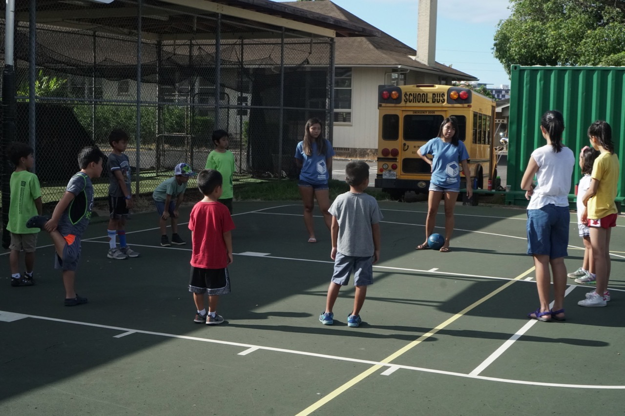kids playing soccer on the basketball court