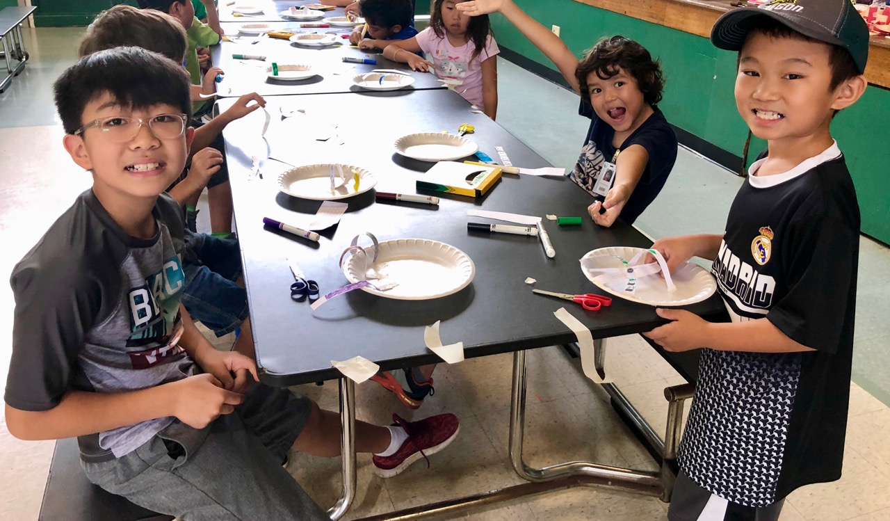 kids working on parachutes at table