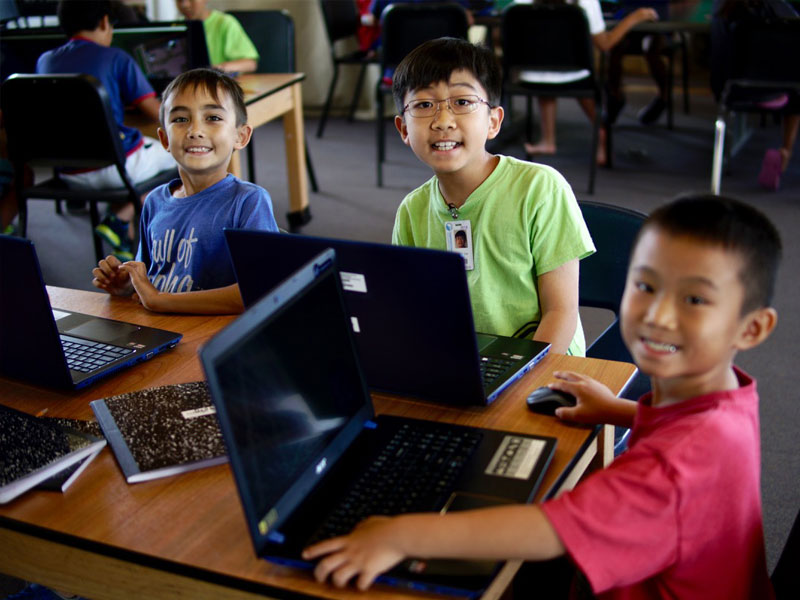 kids smiling for camera playing minecraft